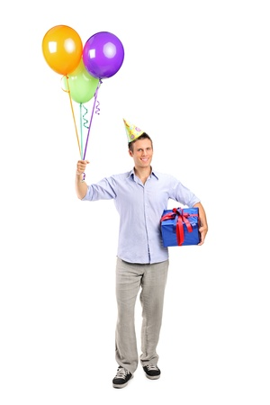 Full length portrait of a smiling young man holding a present and baloons isolated on white Stock Photo - 11264756