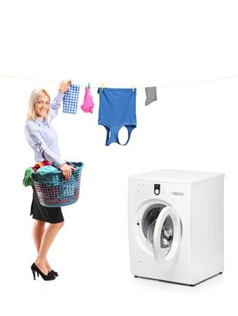 ropa colgada: Mujer joven y sonriente colgar la ropa en el tendedero de ropa al lado de una lavadora aisladas sobre fondo blanco