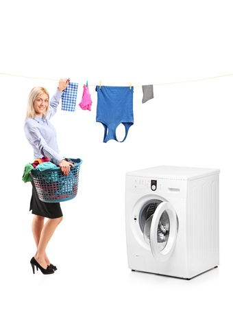 standing in line: Young smiling woman hanging clothes on clothes line next to a washing machine isolated on white background Stock Photo