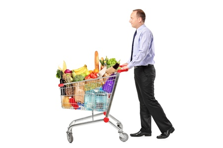 grocery basket: Person pushing a shopping cart full with groceries isolated on white background Stock Photo