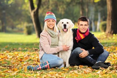 jovenes enamorados: Hombre joven y sonriente y una mujer abrazando a un perro labrador Retreiver en el parque Foto de archivo