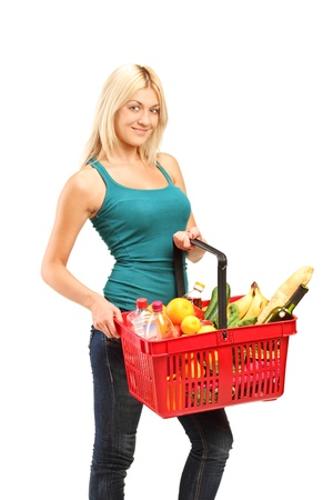 A young woman holding a shopping basket full with groceries isolated on white background photo