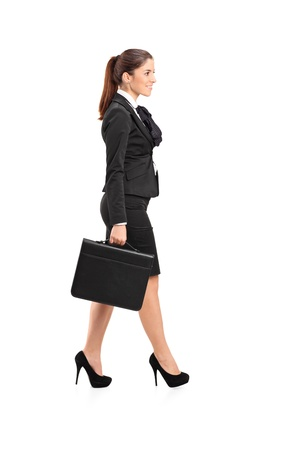 Full length portrait of a businesswoman walking with a briefcase in her hand isolated against white background Imagens