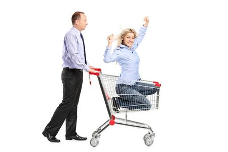 Person pushing a happy woman in a shopping cart isolated against white background photo