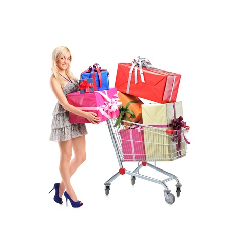 Full length portrait of a female holding  gifts and a shopping cart with many gifts photo