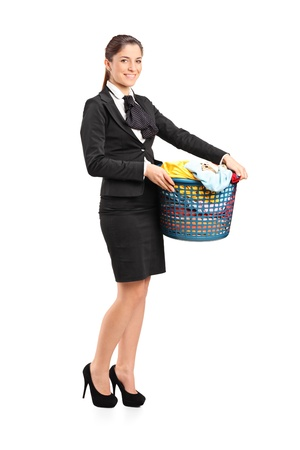 Full length portrait of a female in a suit holding a laundry basket isolated on white background photo