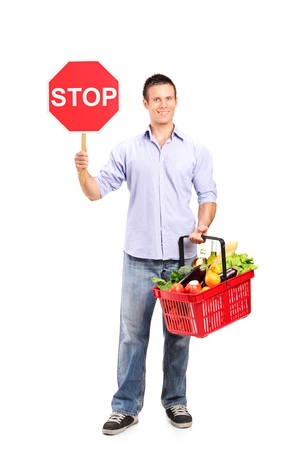 Full length portrait of a male holding a full shopping basket and a stop road sign isolated on white background  photo