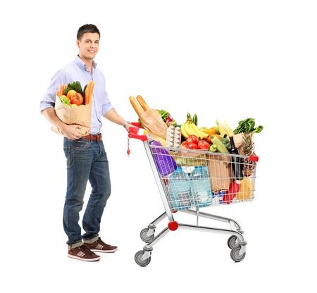 carretilla de mano: Retrato de cuerpo entero de un hombre con una bolsa de plástico y carro de compras aisladas sobre fondo blanco Foto de archivo