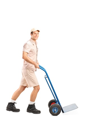 handtruck: Full length portrait of a manual worker pushing an empty handtruck isolated on white background