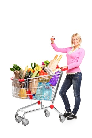 woman shopping cart: Full length portrait of a smiling female showing a credit card and pushing a shopping cart isolated on white background