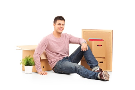 Smiling man resting from moving into a new home with many boxes around him photo