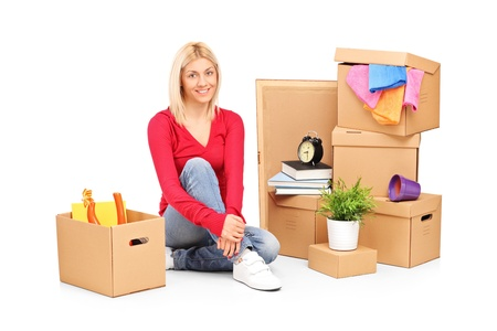 Smiling woman resting from moving into a new home with many boxes around her photo