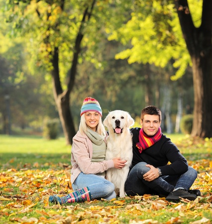 Smiling young man and woman hugging a labrador retreiver dog out in the park photo