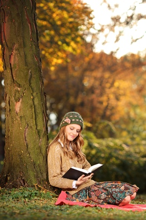 Smiling young woman reading a book in the park photo