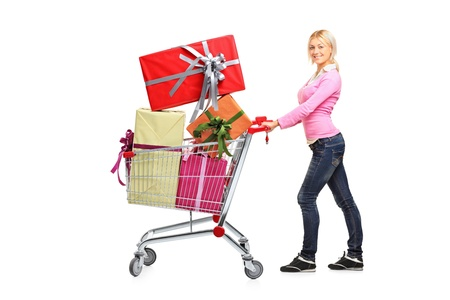 woman shopping cart: Young woman pushing a shopping cart full with gifts isolated on white background