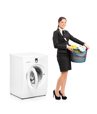 washing clothes: Full length portrait of a smiling woman holding a laundry basket next to a washing machine isolated on white background