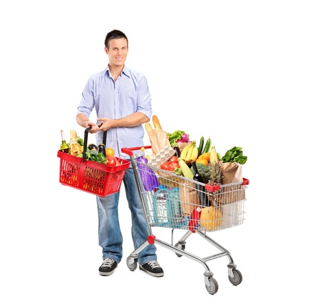 grocery cart: Full length portrait of a young man holding a basket full with products and shopping cart isolated on whte background