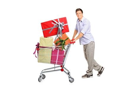 pushing: Jonge man duwen van een winkelwagentje vol met geschenken geïsoleerd tegen witte achtergrond Stockfoto