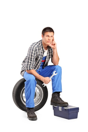 A thoughtfull mechanic sitting on a spare tire and holding a wrench isolated on white background Stock Photo - 11409601