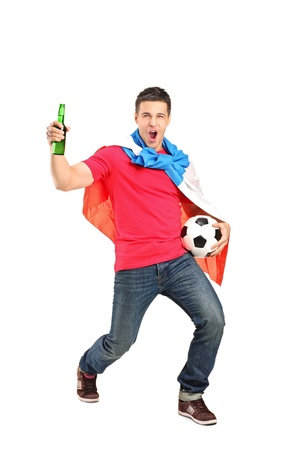 Football fan covered with dutch flag and holding a beer bottle and football cheering isolated on white background photo