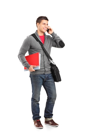 talking telephone: Full length portrait of a smiling school boy holding books and talking on a phone isolated on white background