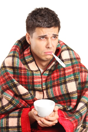 Ill man covered with blanket holding a tea cup and a thermometer in his mouth isolated against white background photo