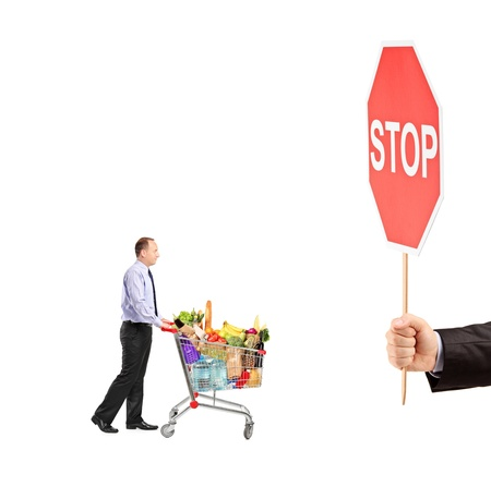 Man pushing a shopping cart full with food and a hand holding a stop sign isolated on white background photo