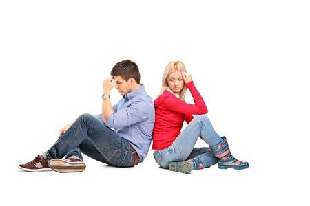 pareja enojada: Pareja sentada de espaldas después de haber tenido una discusión sobre fondo blanco