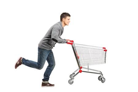 empujando: El hombre joven corriendo y empujando un carrito de la compra vac�o aislado sobre fondo blanco