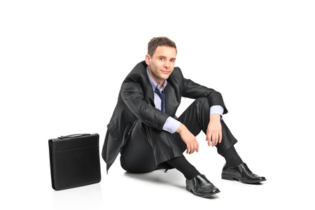 A disappointed businessman and his briefcase isolated on white background photo