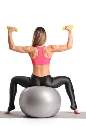 gimnasia aerobica: Una mujer de trabajo con mancuernas sentado sobre una pelota de pilates aisladas sobre fondo blanco