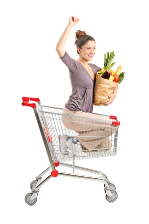 A view of a happy female with a paper bag posing into a shopping cart isolated on white background photo