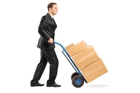 Full length portrait of a businessman pushing a hand truck full with cardboard boxes isolated on white background photo