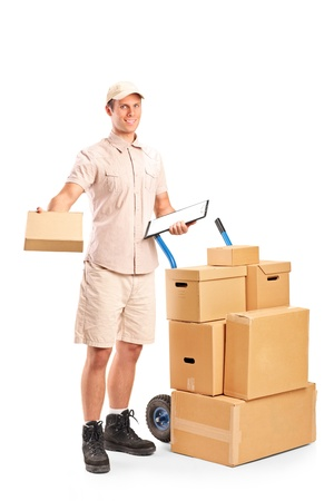 hand truck: Full length portrait of a delivery boy holding a clipboard posing next to a hand truck with stack of boxes isolated on white background