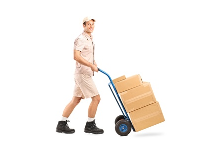 Full length portrait of a delivery boy pushing a handtruck isolated on white background photo