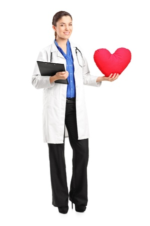 Full length portrait of a female doctor holding a red heart shaped pillow isolated on white background photo