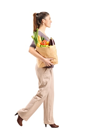 Full length portrait of a female holding a paper bag with groceries isolated against white background photo