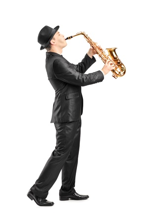Full length portrait of a man in a suit playing on saxophone isolated against background photo
