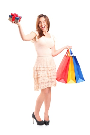 Full length portrait of a smiling woman holding a shopping bags and a gift isolated on white background photo