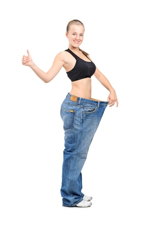 Full length portrait of a weightloss woman giving a thumb up isolated on white background Stock Photo - 11744265