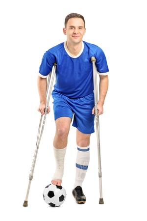 Full length portrait of an injured soccer football player on crutches isolated on white background photo