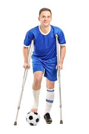 fractura: Retrato de cuerpo entero de un jugador de f�tbol de f�tbol herido con muletas aislados sobre fondo blanco
