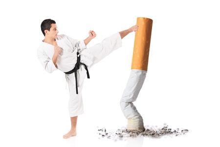 persona fumando: Karate hombre golpeando una colilla de cigarrillo aislado contra el fondo blanco