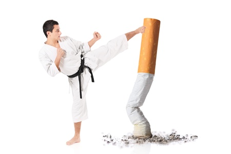 Karate man hitting a cigarette butt isolated against white background photo