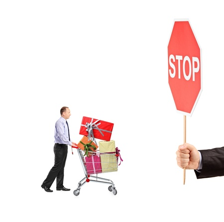 Man pushing a shopping cart full with gifts and a hand holding a stop sign isolated on white background photo