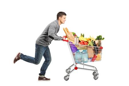 Jonge man lopen en duwen van een winkelwagentje vol met voedsel op een witte achtergrond Stockfoto