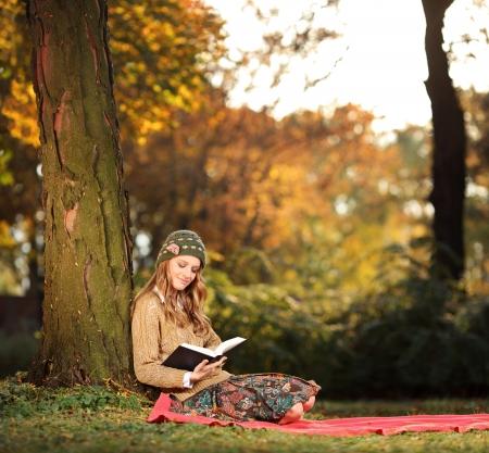 mujer leyendo libro: Joven mujer leyendo un libro en el parque de la ciudad de Skopje, Macedonia
