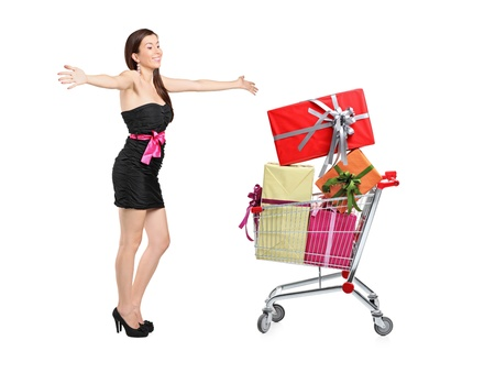 An excited woman poding next to a shopping cart with gifts isolated on white background photo