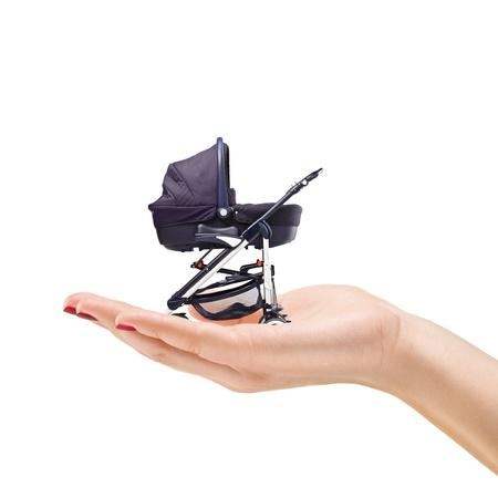 poussette: Belle main manucur�e femme tenant une poussette pour b�b� isol� sur fond blanc Banque d'images
