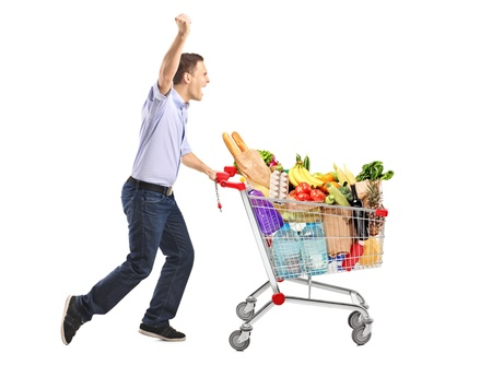 Euphoric man pushing a shopping cart full with food isolated on white background photo